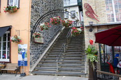 Staircase between buildings. Staircase with a decorative arch with hanging flower pots between buildings, Old Quebec, Quebec City, Canada Stock Photos