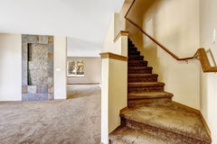 Staircase with carpet steps and wooden railing in empty house Stock Image
