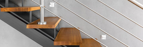 Staircase with chromed railing. Panorama of stylish wooden stairs with chromed railing and decorative grey wall finish in modern interior Royalty Free Stock Image
