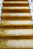 Staircase covered with luxury gold carpet Stock Photography