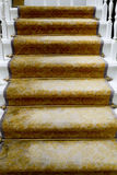 Staircase covered with luxury gold carpet Stock Photos