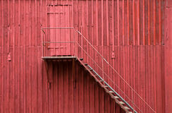 Staircase and door on red wall Royalty Free Stock Photos
