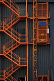 Staircase and elevator. Orange on black background detail of an external elevator and staircase Royalty Free Stock Photo