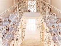 Staircase with marble steps and with ornamental iron handrail. Luxurious interior with gilded decorative nuances Stock Photo