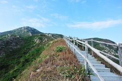 Staircase in mountain. Staircase with handrails in mountain lead to blue sky stock photography