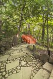 Staircase paved leading to a japanese vermilion bridge surrounde. Spiral staircase paved with stones and pebbles leading to the Japanese vermilion Tsuten bridge stock image