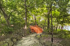 Staircase paved leading to a japanese vermilion bridge surrounde. Spiral staircase paved with stones and pebbles leading to the Japanese vermilion Tsuten bridge royalty free stock images