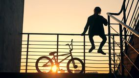 Staircase railing with a male adolescent sitting on it and his bicycle beside him. 4K stock footage