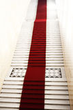 Staircase with red carpet, illuminated by light Stock Photo