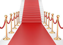 Staircase and red carpet between two gold stanchions with rope Stock Photo