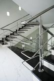 Staircase with a steel handrail. Marble staircase with a steel handrail in a modern building royalty free stock image