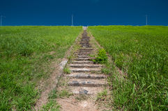 Staircase to the highest point. Staircase between green grass hill with blue sky Royalty Free Stock Photography