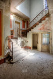 Staircase in a villa. Abandoned villa in Switzerland with a beautiful staircase with lovely red soft colors Royalty Free Stock Photos