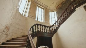 A staircase with wooden railing in an abandoned architectural building. The legacy of past architectural times. Handrail. Stairs made of dark wood stock video