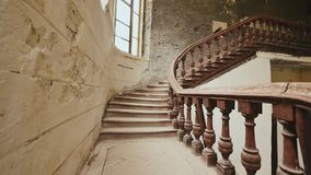 A staircase with wooden railing in an abandoned architectural building. The legacy of past architectural times. Handrail. Stairs made of dark wood. Shooting in stock video