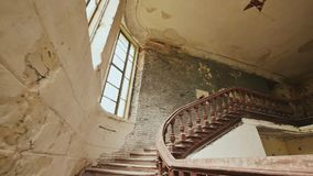A staircase with wooden railing in an abandoned architectural building. The legacy of past architectural times. Handrail. Stairs made of dark wood. Shooting in stock footage