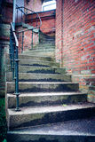 Stairs. Reach the goal with old, winding stairs with a metal railing in a brick building Stock Photo