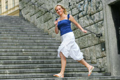 Stairs. Young blonde pretty woman running over stairs Stock Photos