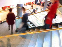 Stairs. People going downstairs in a mall. Sharp golden banister showing the direction at the foreground, first-floor at the background Royalty Free Stock Images