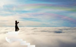 Girl Silhouette on stairs above the clouds rainbow sky straiway to heaven. Stairs above the clouds, spiral stairs to Heaven. Blue sky with white clouds and stock illustration