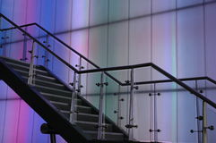 Stairs against a color wall. A modern staircase shown in silhouette against a wall with colored lights. Shot at an angle Royalty Free Stock Photos