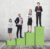 Stairs as a huge green bar chart are in the room with concrete wall and wooden floor. Business people are standing on each step as Stock Images