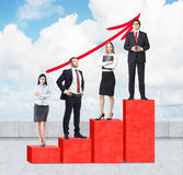 Stairs as a huge red bar chart are on the roof. Business people are standing on each step as a concept of corporate ladder. A grow. Ing red arrow is over cloudy Stock Photo