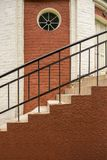 Stairs in a brick house. Round window in the wall. royalty free stock image