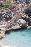 Stairs built on rocks descending to beach. With turquoise water Royalty Free Stock Photography