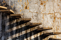 Stairs casting shadow on old weathered wall Royalty Free Stock Photos