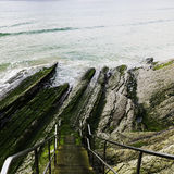 Stairs in the cliff. Stairs with banister descending for the cliff towards the beach in San Sebastian Stock Photos