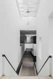 Stairs and a corridor with white walls in  modern building. Stairs and a corridor with white walls in a modern building Stock Image