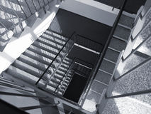 Stairs down. Stairs spiralling down in a high, birghtly lit office building. Monochrome silver oxide simulation. Wide range of tones Royalty Free Stock Image