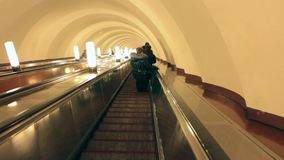Stairs down escalator. Escalator motion silhouette of a person stands at the bottom of the escalator stock video footage