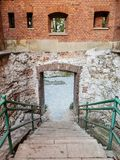 Stairs down with handrails. Stairs leading down to the building. Concrete stairs. Red-painted defensive walls built. Red brick. White stones. Green handrail stock photos