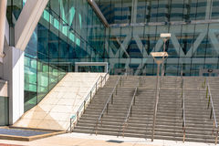 Stairs in front of a glass front building. Flight of stairs leading to the entrance of a glass-front building Stock Photos