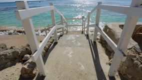 Stairs in front of the ocean on a sunny day and blue sky Royalty Free Stock Image