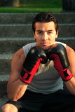 On Stairs With Gloves. An attractive male boxer sitting on steps with his gloves on Royalty Free Stock Images