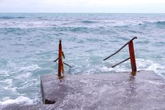 Stairs going into rough sea. Bad day at the beach with big waves. Stairs going into rough sea. Bad day at the beach with big waves royalty free stock image