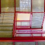 Stairs with grated treads and bright red handrails viewed from below. The flight of stairs is inside a building with white ceiling and wall royalty free stock photography