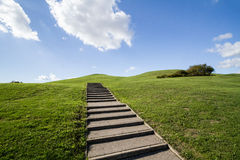 Stairs on a green hill. Stairs leading to the top Stock Photos