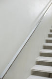 Stairs and hand rails along white wall Royalty Free Stock Photo