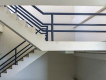 Stairs with handrail to the top or below of the building. White stairs with dark blue handrail to the top or below of the building royalty free stock photo