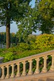 Stairs with handrails in antique style in the park on the background of rich green oak leaves. For your design royalty free stock images