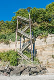 Stairs By The Hill 6. A vertical staircase rises straight up next to a hill at Saltwater State Park in Des Moines, Washington Stock Photo