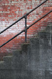 Stairs with Iron Railing and Old Brick Wall. Old concrete staircase with an iron handrail with an old red brick wall in backround royalty free stock image