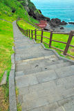 Stairs leading down to the sea. Long flight of stairs leading down to the sea surrounded by mountains and wilderness Royalty Free Stock Photos