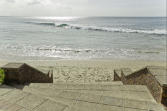 Stairs leading onto the beach. Flight of stairs leading onto the beach with gentle waves breaking Stock Photo