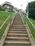Stairs leading up. Concrete staircase leading up the hill to the houses Royalty Free Stock Image