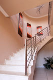 Stairs leading up from entrance hall. Stairs leading up to upper bedroom in upmarket South African home, paintings on wall with chandeliers Royalty Free Stock Photo